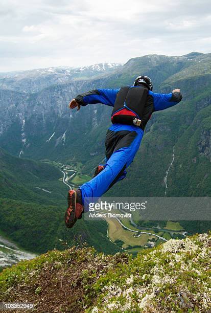 Base jumper leaping from cliff in Norway
