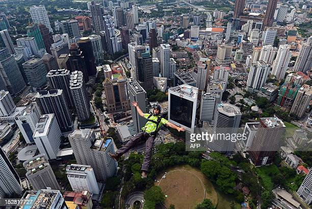 Base jumper Luke Miller from Australia leaps from the top of the 421metre Kuala Lumpur Tower during the International Tower Jump in Kuala Lumpur on...