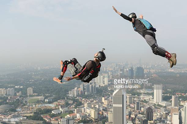 Base jumpers Annette O'Neil and Bret Kistler of the US leap from the 300metre high Open Deck of Malaysia's landmark Kuala Lumpur Tower during the...