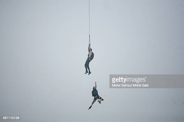 Base jumpers shrouded in haze leap from the 300metre high open deck at Malaysia's Kuala Lumpur Tower during the International Tower Jump on October 3...