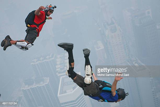Base jumpers shrouded in haze shrouded in haze leap from the 300metre high open deck at Malaysia's Kuala Lumpur Tower from the 300metre high open...
