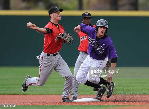 Base runner Ross Kivett of the Kansas State Wildcats is safe at second base as shortstop Kelby Tomlinson of the Texas Tech Red Raiders makes a throw...