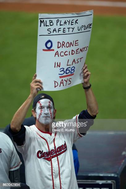 ALDS Playoffs Cleveland Indians fan with face painted and holding up sign in stands that reads MLB PLAYER SAFETY UPDATE 0 DRONE ACCIDENTS IN LAST 368...