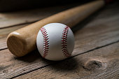 baseball and baseball bat on wooden table background, close up