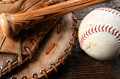 A top view image of an old used baseball, baseball glove, and baseball bat.