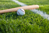 Baseball and bat on grass field with white stripe. Low angle view with defocused foreground and background.Some others you may also like: