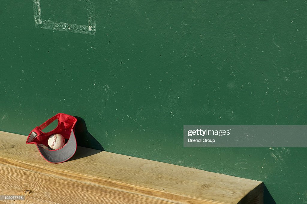 A baseball and cap on a dugout bench