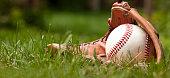 Photo of an Baseball ball and glove on green grass. Outdoor scene