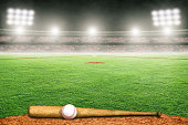 Baseball bat and ball on field at brightly lit fictitious outdoor stadium. Focus on foreground and shallow depth of field on background and copy space.