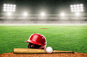 Baseball helmet, bat and ball on field at brightly lit fictitious outdoor stadium. Focus on foreground and shallow depth of field on background and copy space. Stadium created in Photoshop.