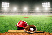 Baseball helmet, bat, glove and ball on field at brightly lit fictitious outdoor stadium. Focus on foreground and shallow depth of field on background and copy space. Stadium created in Photoshop.