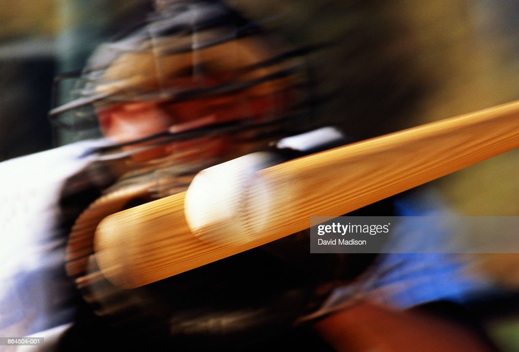 Baseball, bat hitting ball, catcher standing behind (blurred motion)