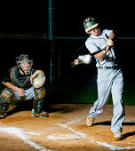 Amazing photo of a baseball ricocheting off of the batter's bat at home plate on a baseball diamond. Lime dust explodes off the ball after contact. Catcher in background is poised to catch the ball ju
