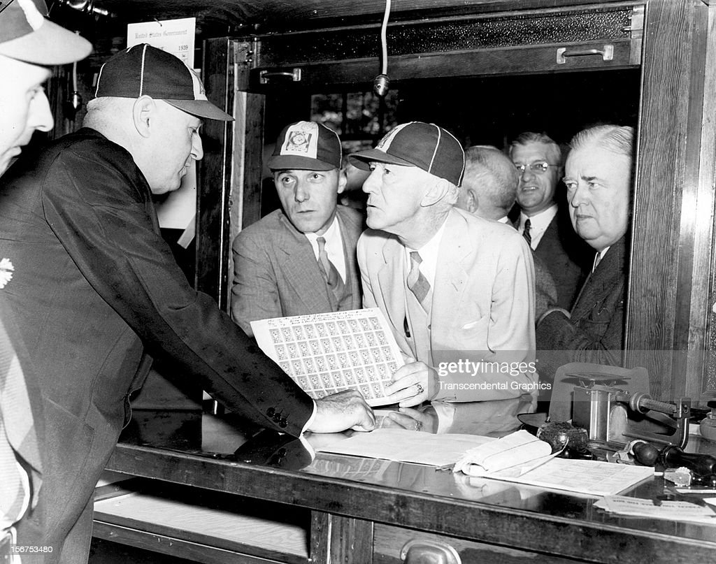Baseball bosses Ford Frick, left, and Judge Landis purchase postage stamps commemmorating the inaugural weekend for the Baseball Hall of Fame on June 12, 1939 in Cooperstown, New York.