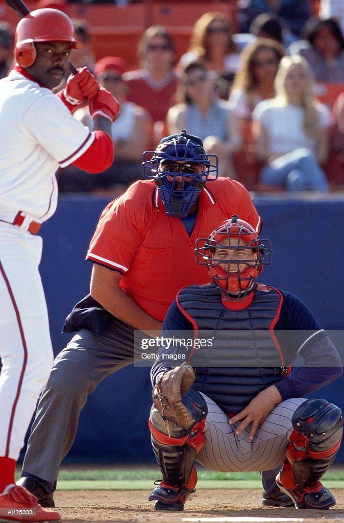 Baseball catcher giving sign, batter getting set for pitch