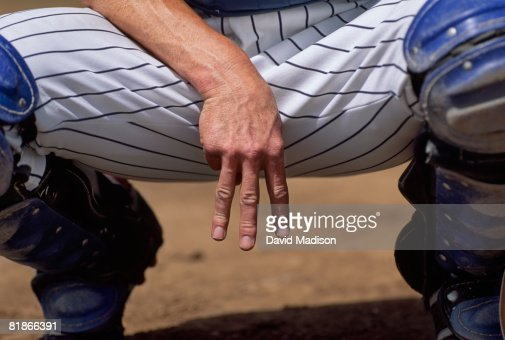 Baseball catcher signaling pitcher his recommended pitch.
