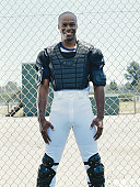 Baseball catcher standing, smiling, portrait