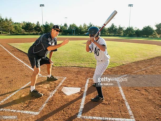Baseball coach and boy (10-11) standing on baseball diamond