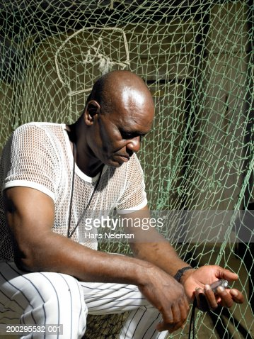 Baseball coach looking at stopwatch, side view