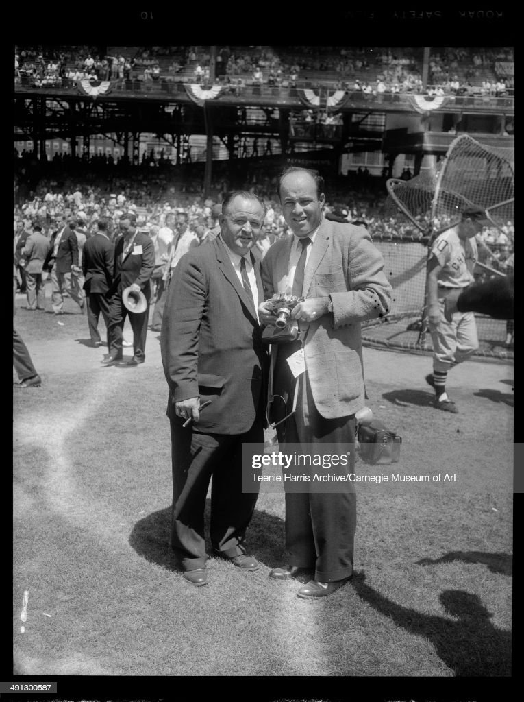 Baseball commentator Joe Garagiola holding camera, standing with unknown man at Forbes Field for 1959 All Star Game, Pittsburgh, Pennsylvania, July 7, 1959.