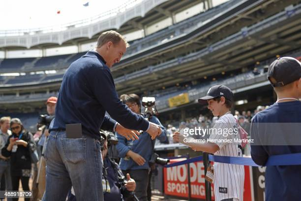 Denver Broncos QB Peyton Manning signing autographs for youth fans before New York Yankees vs Tampa Bay Rays game at Yankee Stadium Bronx NY CREDIT...