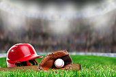 Low angle view of baseball helmet, bat, glove and ball on field grass and deliberate shallow depth of field on brightly lit stadium background with copy space. Fictitious stadium background was create