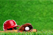 Low angle view of baseball equipment on field with close up dew on grass and deliberate shallow depth of field on background with copy space.