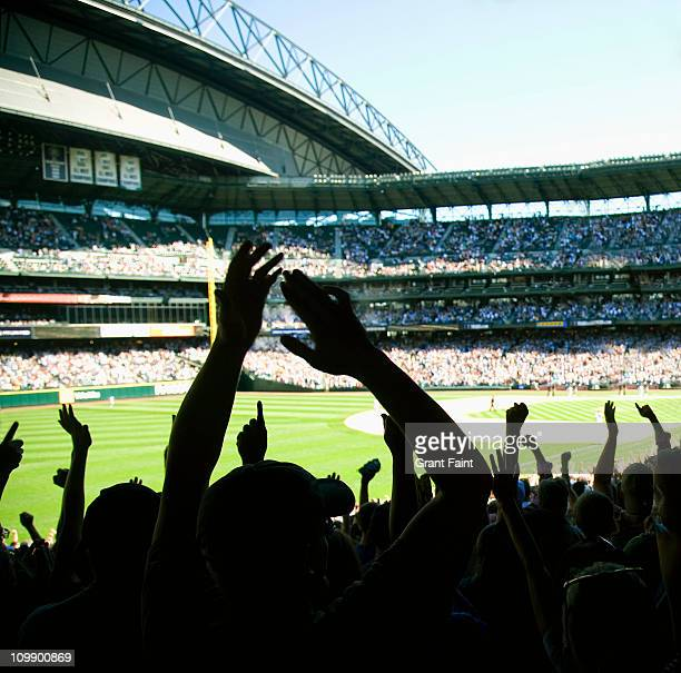 Baseball fans cheering in stadium.