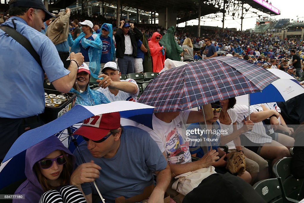 Baseball fans huddle under umbrellas as ran comes down during the first inning as the Chicago Cubs play host to the Philadelphia Phillies on Friday, May 27, 2016, at Wrigley Field in Chicago.