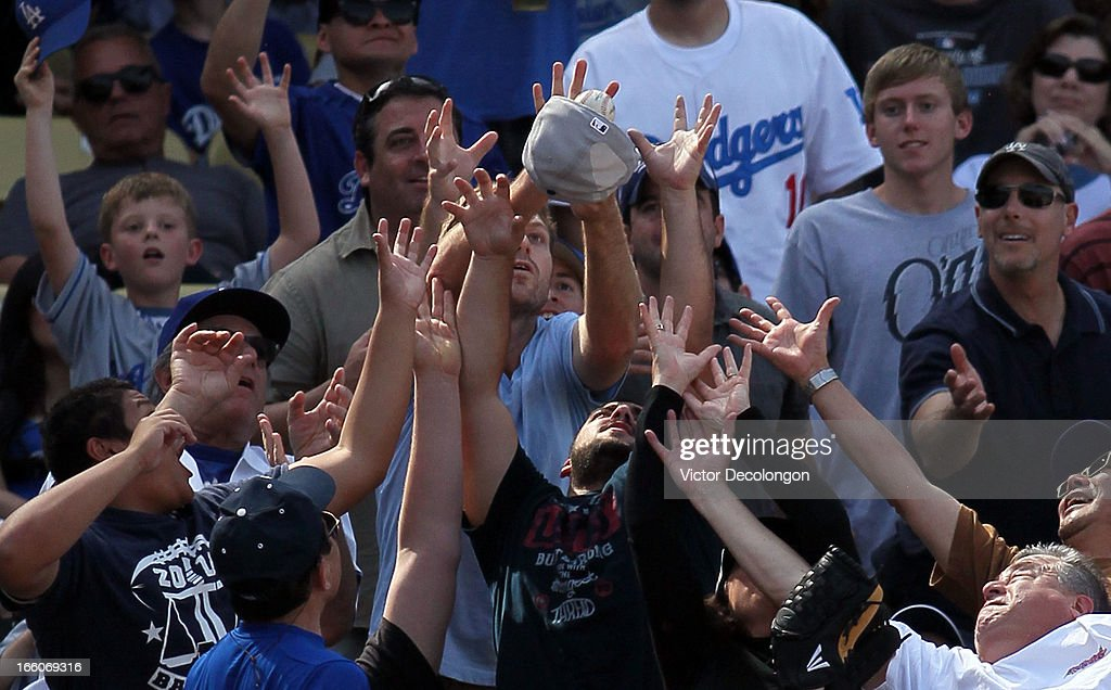 Baseball fans reach for a foul ball in the stands in the seventh inning during the MLB game between the Pittsburgh Pirates and the Los Angeles Dodgers at Dodger Stadium on April 7, 2013 in Los Angeles, California. The Dodgers defeated the Pirates 6-2.