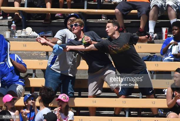 Baseball fans reach to catch the home run ball hit by Cody Bellinger of the Los Angeles Dodgers in the game against the Colorado Rockies at Dodger...