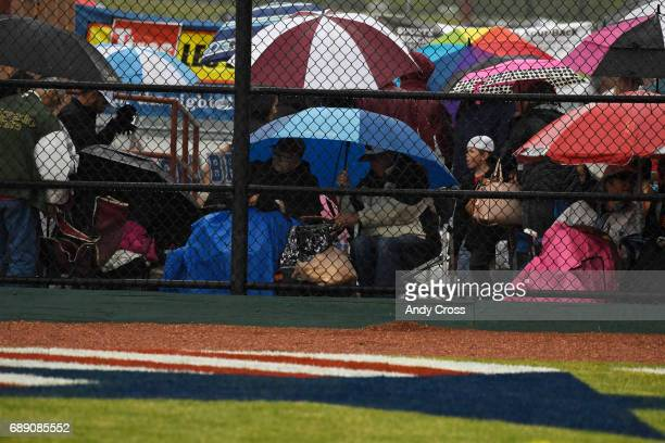 Baseball fans seek shelter underneath umbrellas during the Colorado State 5A championship game featuring the Rocky Mountain Lobos and the Broomfield...