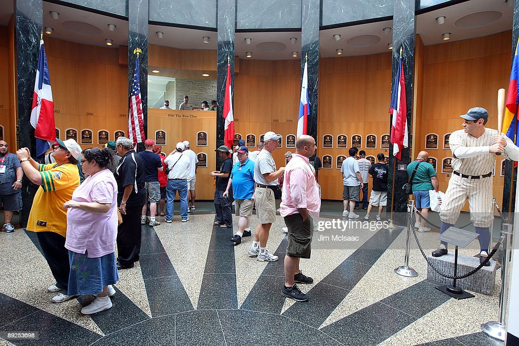 Baseball fans view the plaques of inducted players at the National Baseball Hall of Fame during induction weekend on July 25 2009 in Cooperstown New...