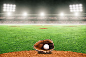 Baseball glove and ball on field at brightly lit fictitious outdoor stadium. Focus on foreground and shallow depth of field on background and copy space. Stadium created in Photoshop.