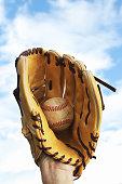 a baseball glove and ball on a blue sky background.