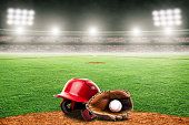 Baseball helmet, glove and ball on field at brightly lit fictitious outdoor stadium. Focus on foreground and shallow depth of field on background and copy space.  Stadium created in Photoshop.