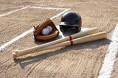 Baseball glove, balls, bats and baseball helmet at home plate