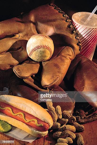 Baseball glove , hot dog , peanuts and soda