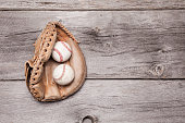A worn catchers mitt with two baseball inside of it sits on a rustic wooden background.