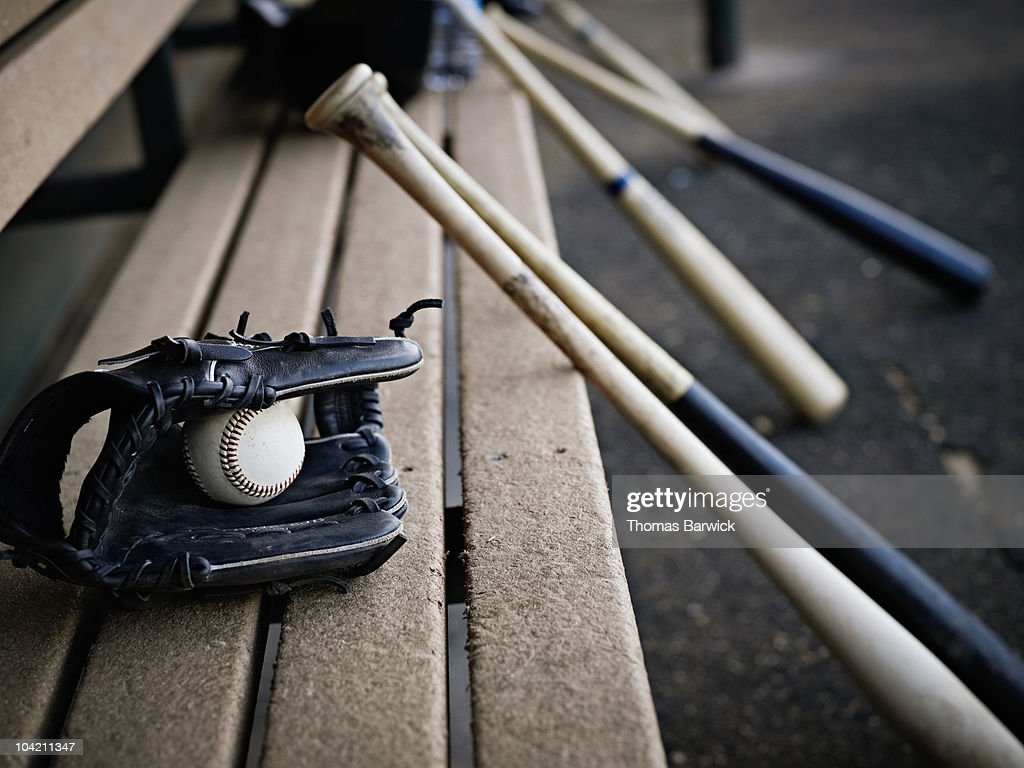 Baseball glove with ball and bats in dugout : Stock Photo