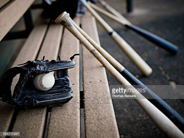 Baseball glove with ball and bats in dugout
