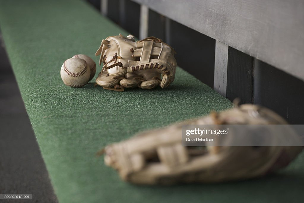 Baseball gloves and balls on bench in dugout