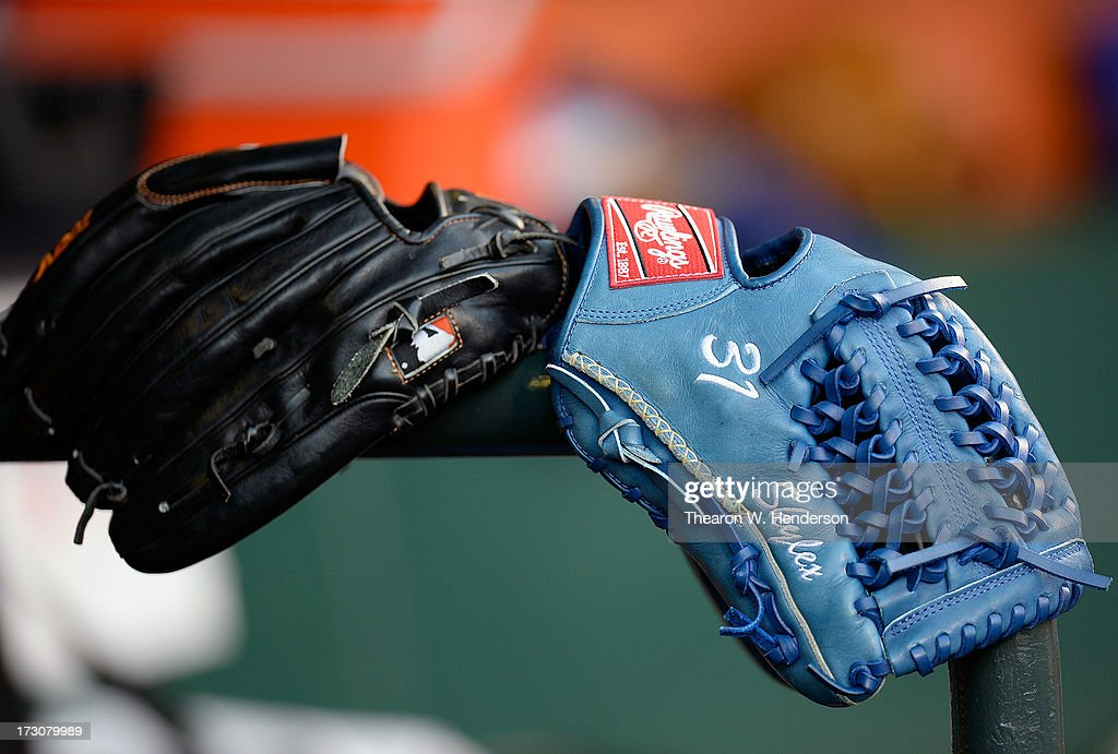 Baseball gloves belonging the the Los Angeles Dodgers sits on the rail in the dugout against the San Francisco Giants at AT&T Park on July 5, 2013 in San Francisco, California.