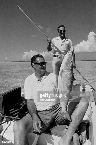 Baseball great Ted Williams holds up a bonefish in the Bahamas while George Hommel poles the boat