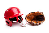 Baseball equipment consisting of red helmet, leather glove and baseball. Isolated on white background.