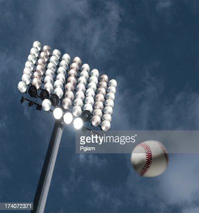 Beisebol casa execução sob as luzes do estádio