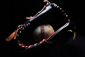A baseball and glove stand isolated from the background.