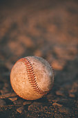 An old baseball in the dirtAn old baseball in the dirt