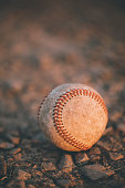 An old baseball in the dirt