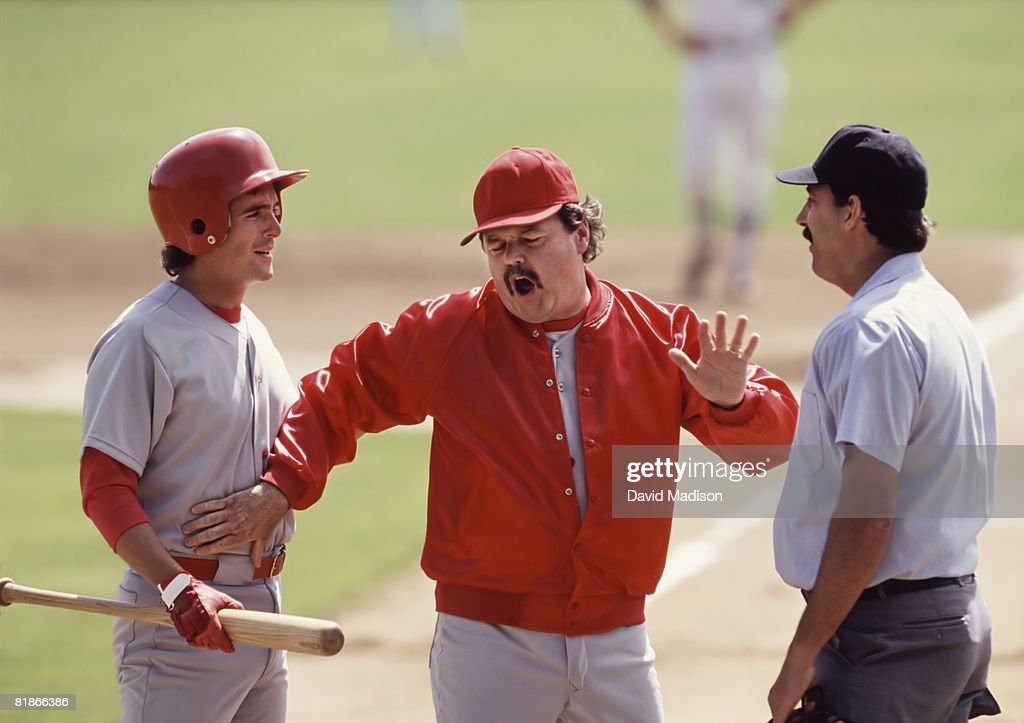 Baseball manager arguing with umpire and holding back player.